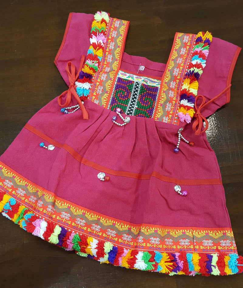 Girl's Hill Tribe Tunic Dress with rainbow pompom trims and traditional tapestry. Pink.