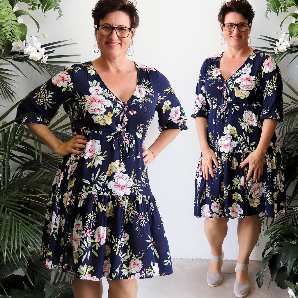 Women's below-the-knee Summer Dress in a floral print. V-Neck with 3/4 sleeves + drawstring around waist. Navy Blue.
