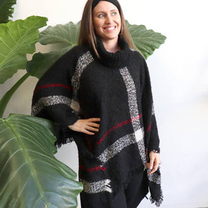 Warm winter women's Poncho, with thick and soft roll-neck top. Easy throw on one-size knit, in a classic striped print. Made with no itch acrylic.  Essential Black.