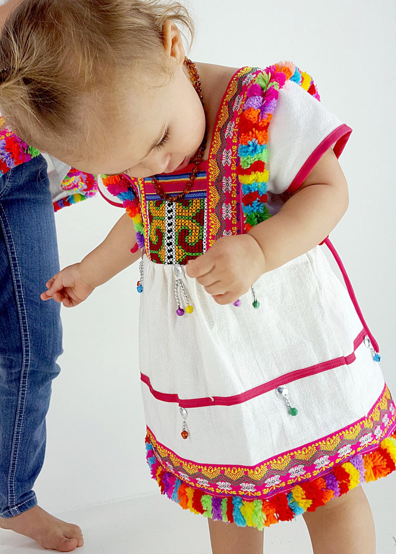 Girl's Hill Tribe Tunic Dress with rainbow pompom trims and traditional tapestry. White.