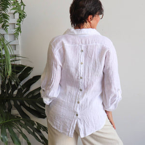 Pure Italian linen women's blouse. Summer top features a mother-of-pearl button feature on the back and roomy cut to sleeves. Available in sizes M-XL. White.