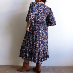 Jessie's Girl Midi Dress is a romantic floral design with all the retro romance of a classic boho style. Navy Blue. Back view.