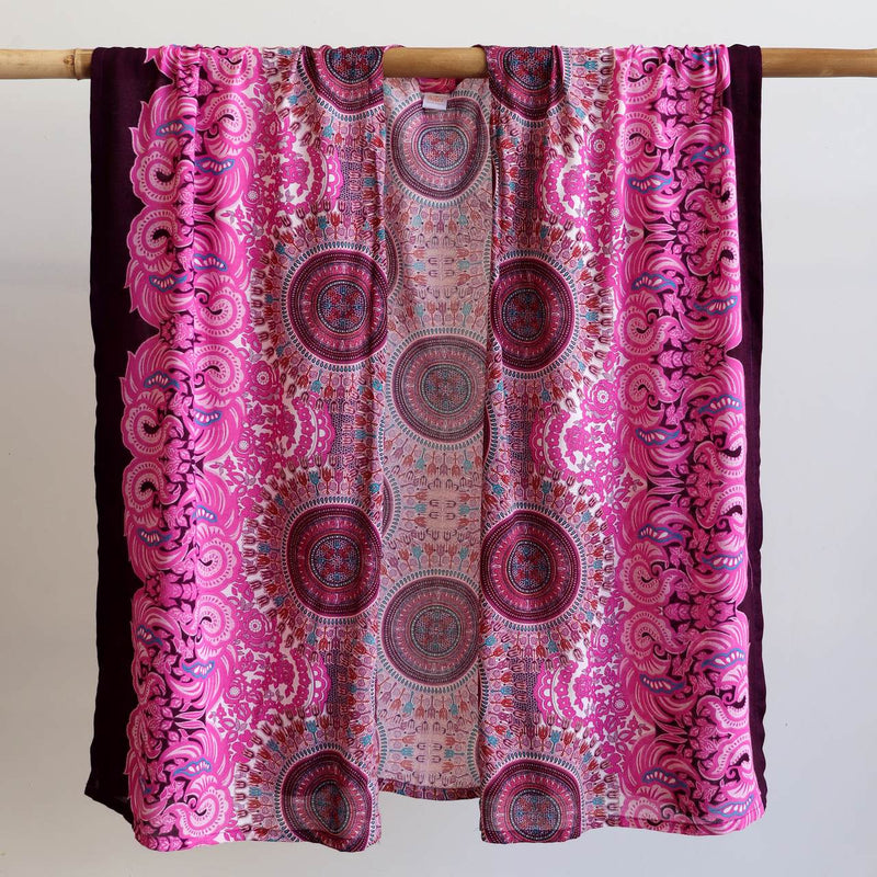 Versatile & lightweight wrap made in a vibrant rayon fabric. Free size garment with a flatlay width of 110cm. Pink.