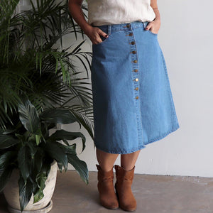 Blue denim a-line skirt falling below the knees and a full button through front and two back pockets.