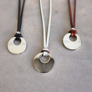 Silver Moon-shaped pendant combined with a natural leather band, available in 3 colours, Black, Silver and Tan.