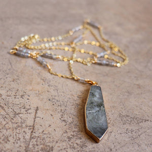 Stone pendant with faceted glass bead features along a fine gold-plated chain. Smokey Quartz.