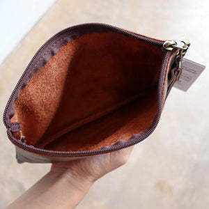 Handmade genuine leather clutch with zippered closure, separate side compartment with wrist strap. Fits your phone, keys and wallet too.