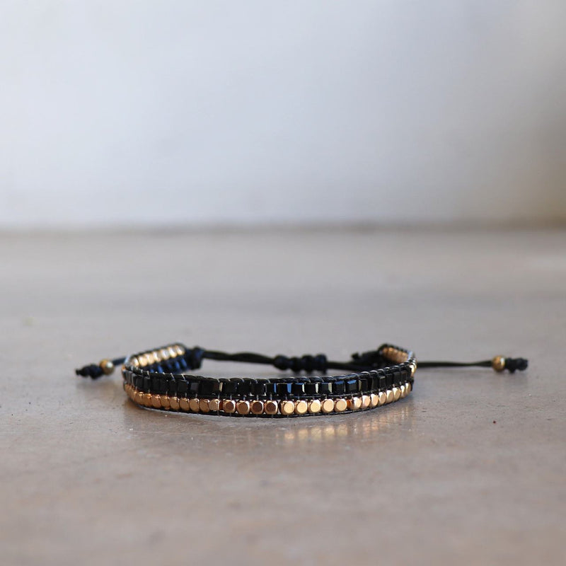 Classic art deco styling, featuring two rows of fine brass and glass beads all hand-knotted using traditional ethnic techniques. Gold & Black.