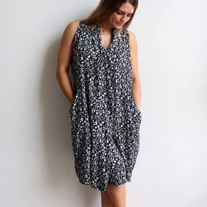 Origami Dress in floral print is a sleeveless trapeze sundress in black or navy blue. Pockets view.
