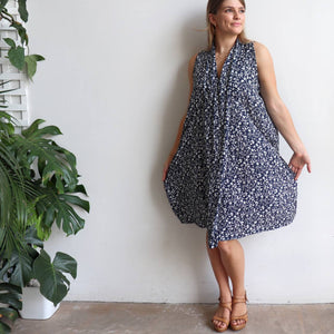 Origami Dress in floral print is a sleeveless trapeze sundress in black or navy blue. Hemline view.
