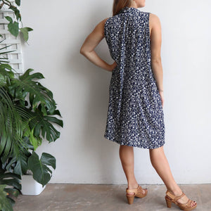 Origami Dress in floral print is a sleeveless trapeze sundress in black or navy blue. Back view.