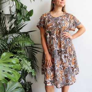 Savvy Sun Dress in animal print is a loosely styled summer dress with short sleeves and below-the-knee hemline fitting up to plus size. Brown.