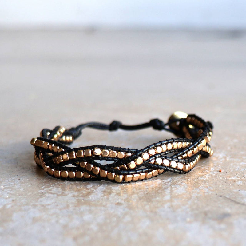 Three-strand, hand-knotted, metallic bead bracelet. Button style closure with 3 size options. Black/Gold.
