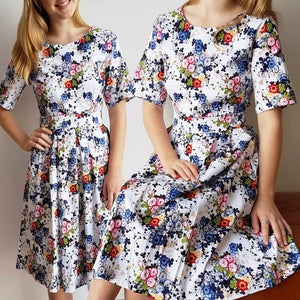 Spring Carnival dress knee-length short sleeves + vibrant floral pattern.