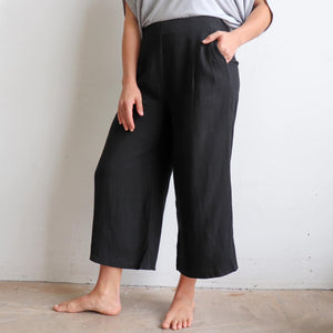 Stradbroke Pants 3/4 length wide-leg women's pants. Made with neat front pleats, two side pockets & elasticated at back of waistband for comfort. Easy care linen/viscose fabric blend. True to fit sizing, available in 8-18. Black.