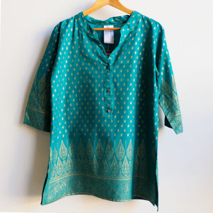 Sunshine Kurta Tunic manufactured in a striking temple themed patterned print. Ethically handmade + produced in lightweight cotton with a mid-length sleeve. Available in sizes S-XXXL. Teal.