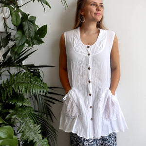 Take It Easy women's button-through sleeveless tunic top. Perfect summer travel shirt made from 100% cotton with handy side pockets. Sizes S/M-L/XL. White.