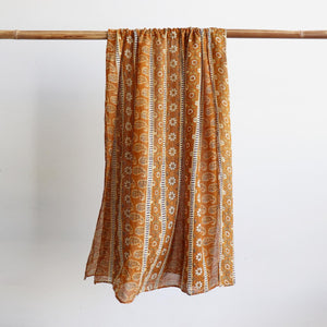 Made with 100% cotton voile fabric, a feminine and floaty oversized scarf. An eye catching traditional print that can also be worn as a beach sarong. Indigo Mustard Yellow.