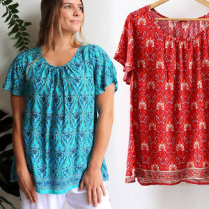 Women's peasant style  Summer Top in a Janaki Print. With short sleeves and hip length hemline it's a perfect casual warm weather top. Made from quality rayon fabric, Sizes 10-22. Turquoise Blue + Rust Orange.