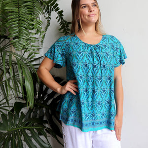 Women's peasant style  Summer Top in a Janaki Print. With short sleeves and hip length hemline it's a perfect casual warm weather top. Made from quality rayon fabric, Sizes 10-22. Turquoise Blue.