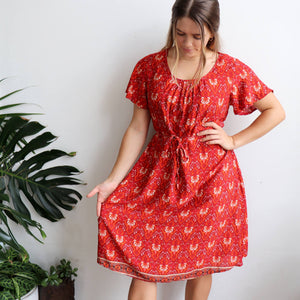Women's Summer Dress in a Janaki Print. With short sleeves, knee length hemline & removable belt it's a perfect casual warm weather dress. Made from quality rayon fabric, Sizes 10-22. Rust orange and red.