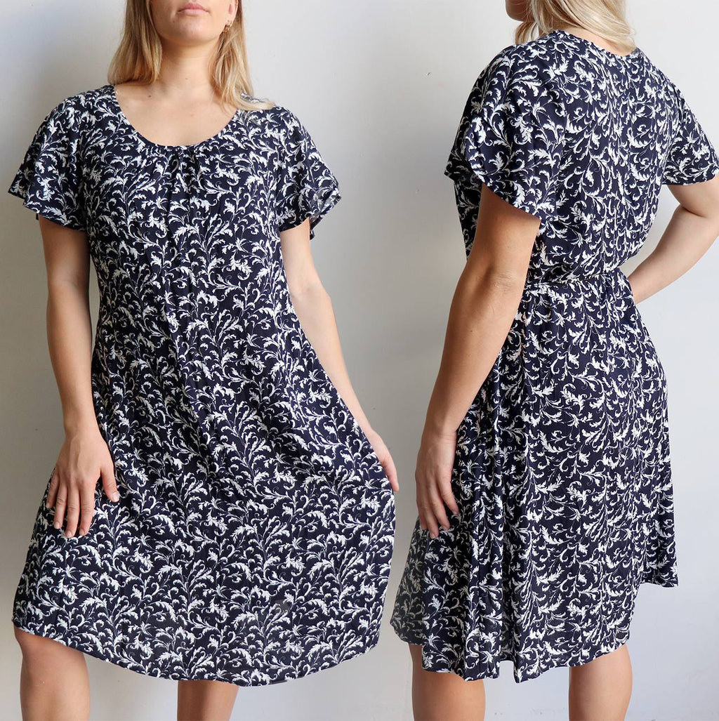 Cool + flowing peasant style women's dress. Short sleeved with knee-length hemline summer dress with removable tie belt. Made with soft, draping rayon fabric.  Navy blue.