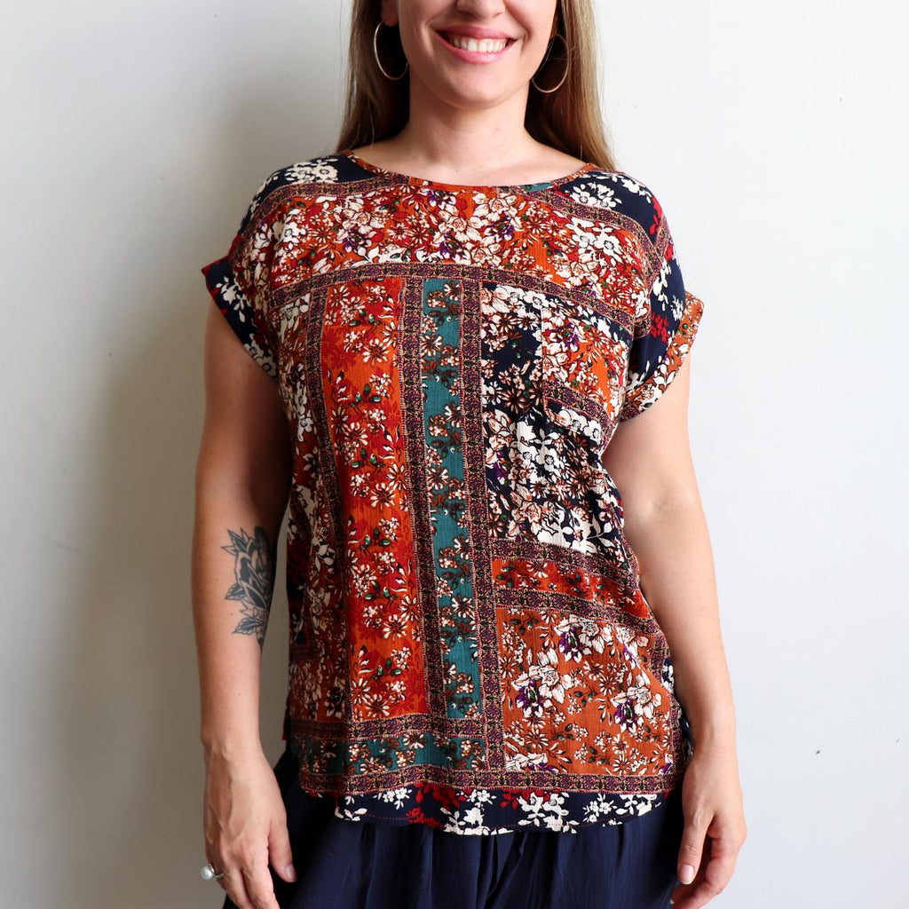 Classic short sleeve blouse top in a caramel, emerald, rust, berry & navy print. Made with soft, lightly textured rayon & featuring a neat scalloped hemline it can be worn tucked in or out.