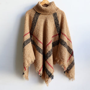 Warm winter women's Poncho, with thick and soft roll-neck top. Easy throw on one-size one-size knit, in a classic striped print. Made with no itch acrylic. Camel.