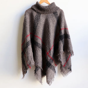 Warm winter women's Poncho, with thick and soft roll-neck top. Easy throw on one-size knit, in a classic striped print. Made with no itch acrylic.  Storm Grey.