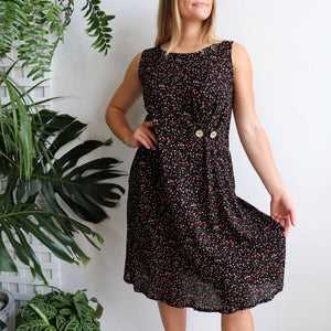 Torquay Dress designed to be loose and flowing with below the knee hemline + a-line cut. Women's summer dress in a rose print fabric with button feature and pockets. Made from lightly textured quality rayon in sizes 8-20. Midnight.
