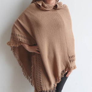 Our 'Whistler Poncho' with the added hood combining a detailed knitted pattern and finishing tasselling. Camel.