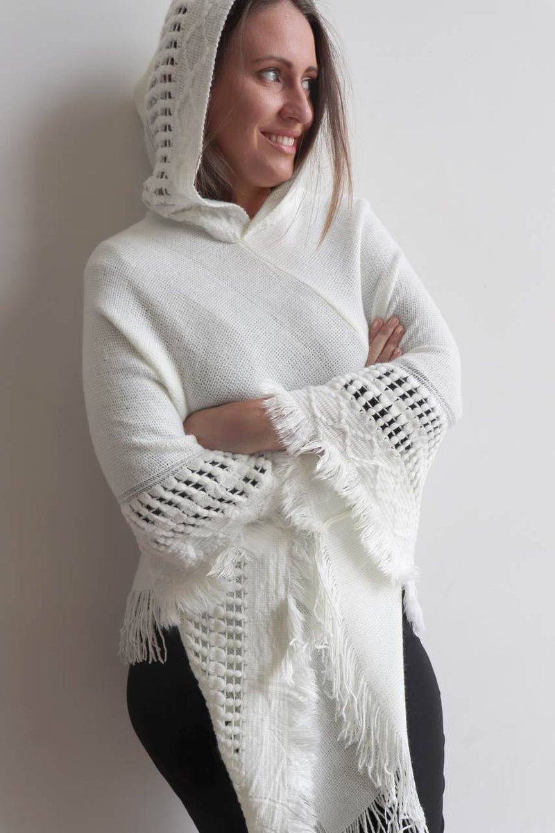 Our 'Whistler Poncho' with the added hood combining a detailed knitted pattern and finishing tasselling. White.