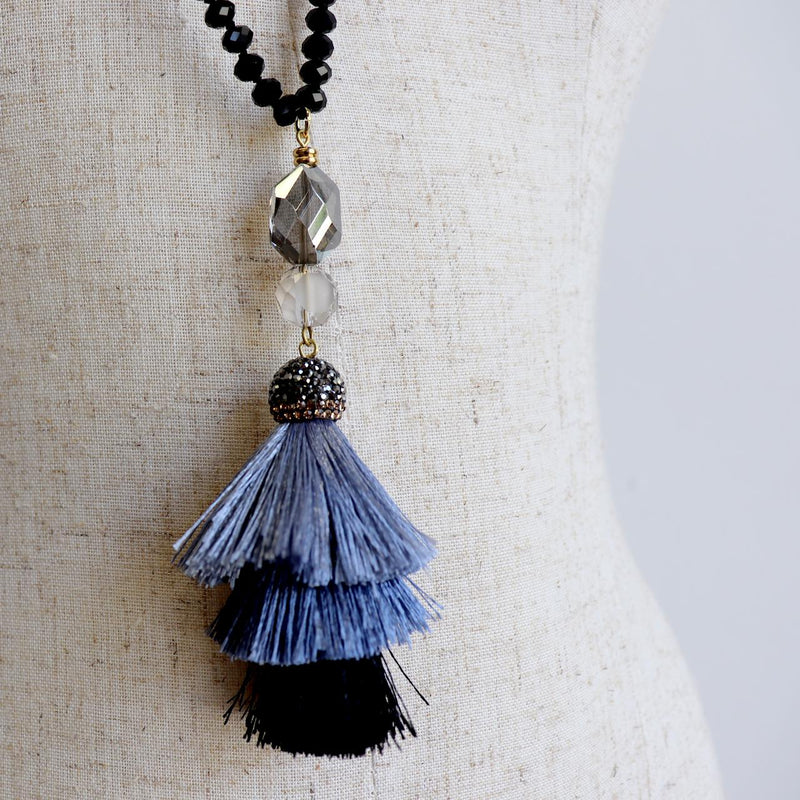 Zeta Necklace is handknotted with cut glass beads and features a tiered tassel pendant in smokey greys.