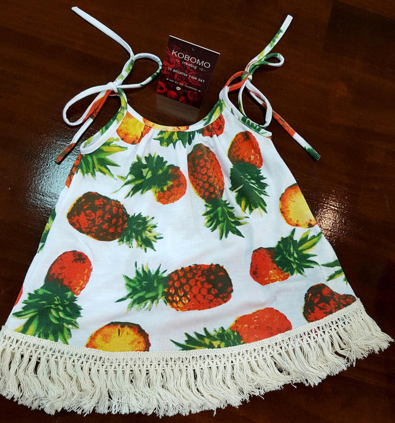 9d64b78561f9 ... Girl s Sun Dress with tropical pineapple print and cotton fringe.  Handmade by our Kobomo team