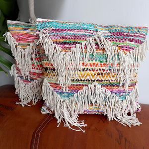 An eclectic throw cushion in natural cotton with a rainbow of fabric woven into it. Boho living style.  50cm x 50cm and has a zippered, removable cover.