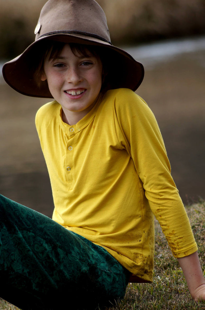 Classic long sleeve t-shirt top for boys and girls. Comfy staple with snap button feature. Sizes to fit newborns, toddlers, kids and tweens up to 10 years old. Ethically handmade with soft, stretch bamboo spandex. Sunshine Yellow