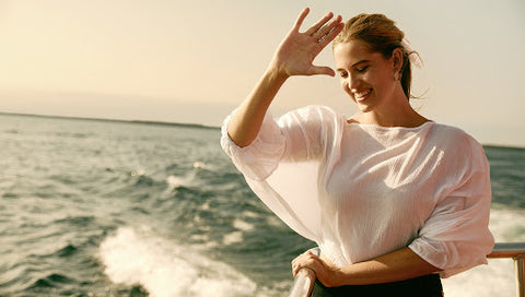 Model on a boat at sunset, hand raised to the camera while smiling