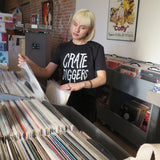 woman wears black Crate Diggers t-shirt, while looking at vinyl records in a record store