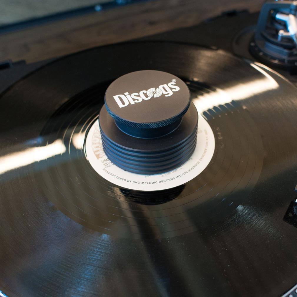 Vinyl record playing with turntable weight