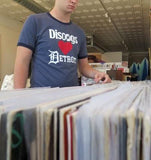 Vinyl records in foreground with person wearing blue 'Discogs Loves Detroit' t-shirt