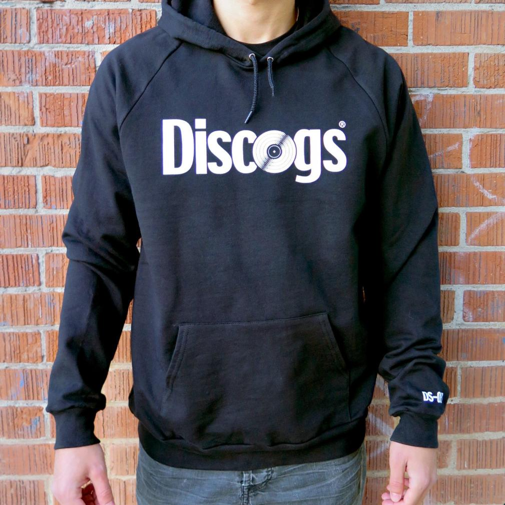 Model wears black Discogs hoodie with catalog number on left sleeve