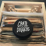 Crate Diggers-branded turntable weight on top of records in crate