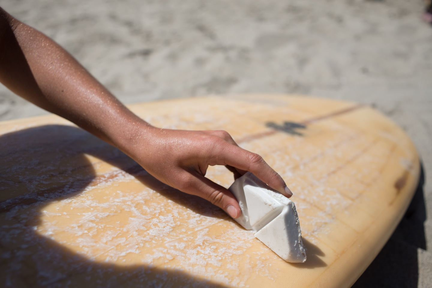 Close up of woman waxing her surfboard