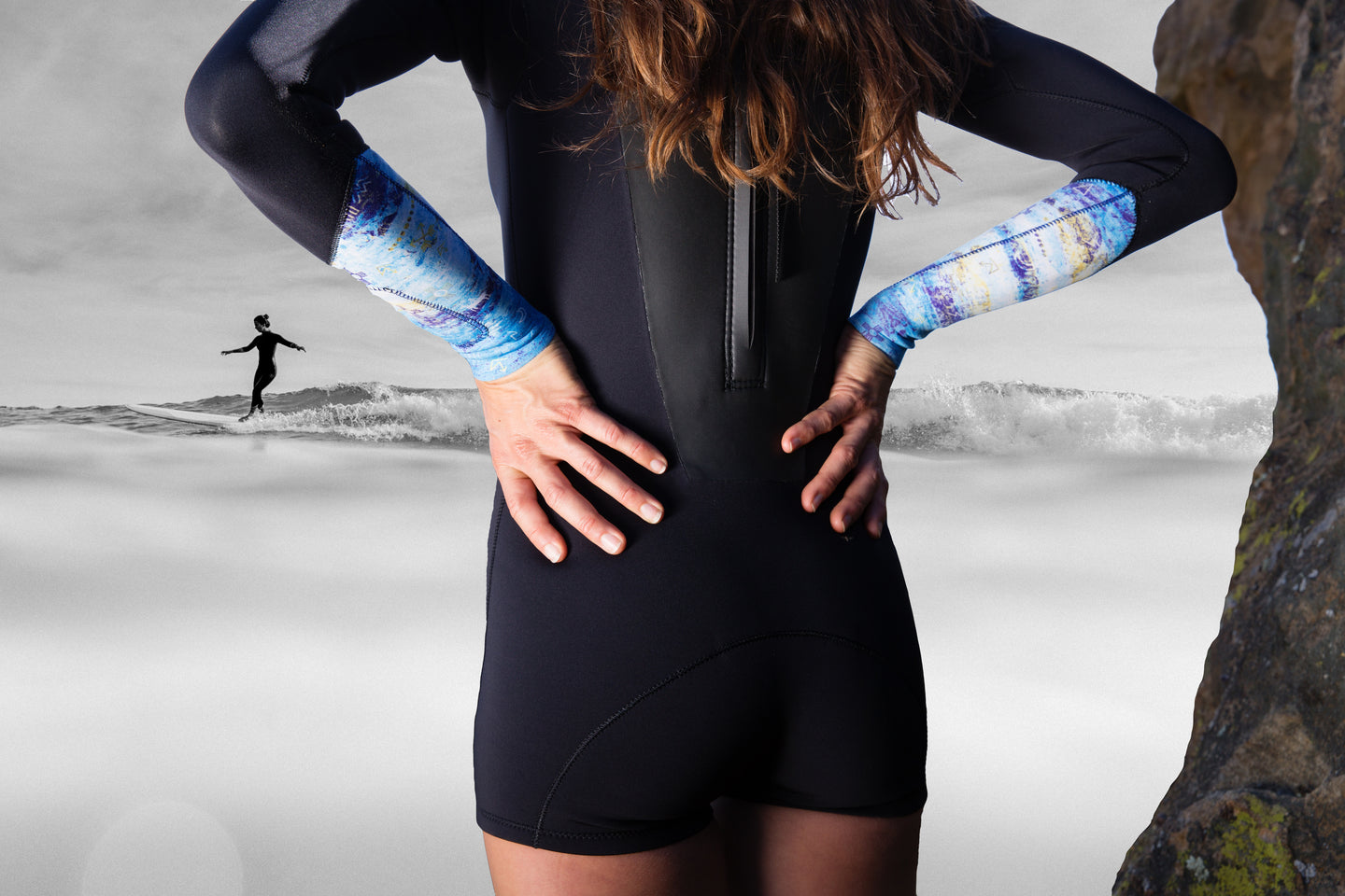 Back of woman wearing wet suit looking at the ocean