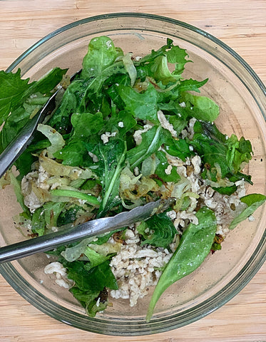 Green salad bowl with chicken, spinach, fennel, mixed greens.