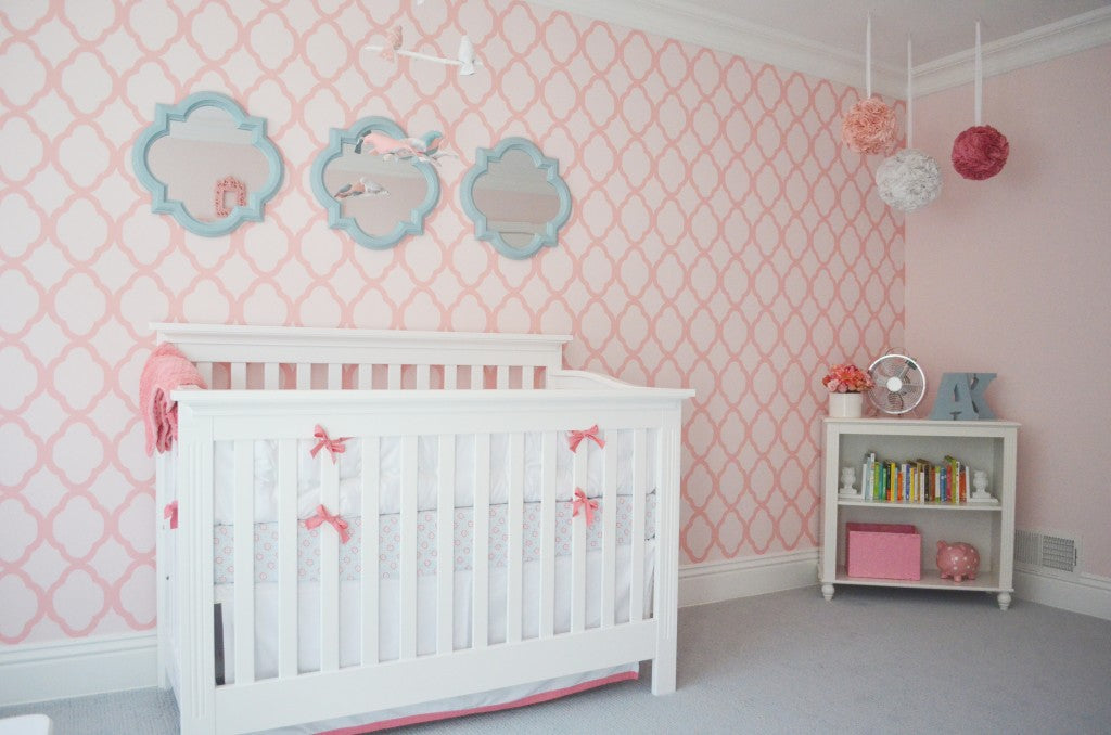 Ceiling poms in a pink, coral, and aqua baby nursery