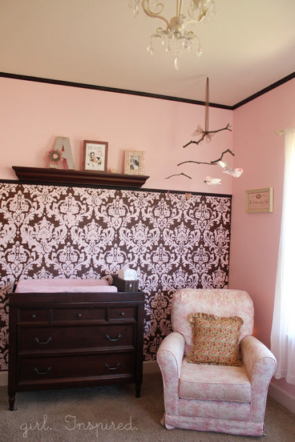 brown and pink damask wallpaper in a baby room