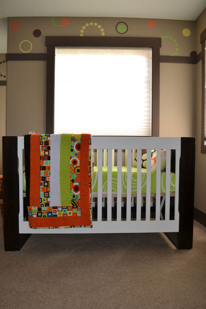 A White Modern Crib with Orange and Green Accents