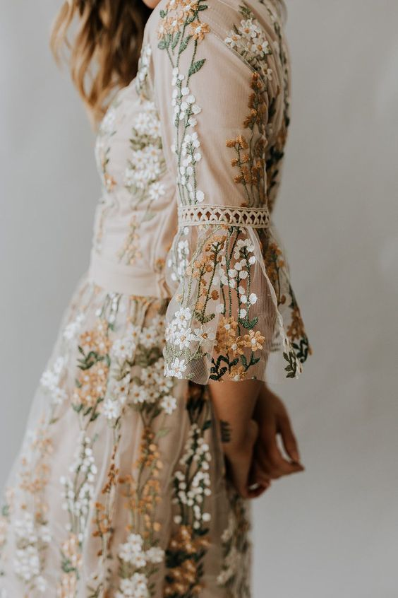Fair skinned person's profile wearing a cream floral embroidered tulle dress with ruffle sleeves