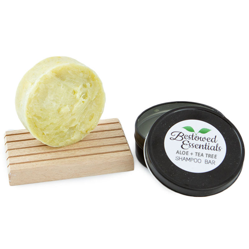 Yellow green round shampoo bar sitting on top of a wooden block next to a black container